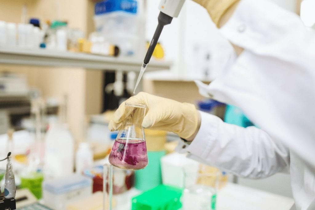 Chemical Exposure/Inhalation Risks and Symptoms A person wearing a white lab coat and latex gloves uses a dripper to add a solution to a glass beaker containing a reddish liquid.