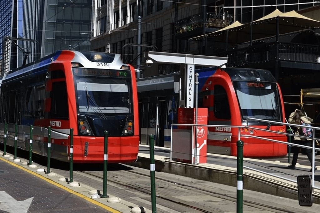 Impacts of New Technology on Public Transportation A pair of red metro trains at a stop in the city