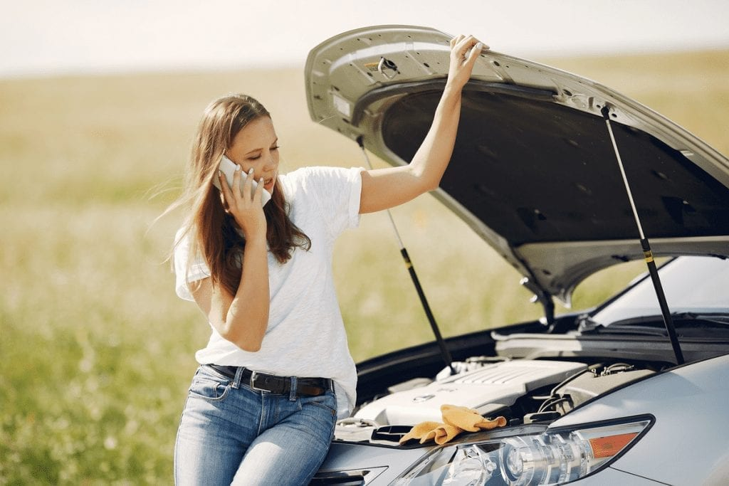 What Should You Keep in Your Car in Case of a Traffic Accident A woman in jeans and a white shirt sits on the front of her car with the hood open, making a call on her cell phone